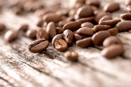 Lage hoek weergave van een hoop verse geroosterde koffiebonen liggend op een oude rustieke houten oppervlak, ondiepe DOF met copyspace. Stockfoto