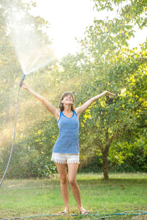 water splashing: Cheerful young woman spraying herself with water on a hot summer day holding the hosepipe above her head as she stands in a beam of warm light from the sun peeking through the leaves of the trees. Stock Photo