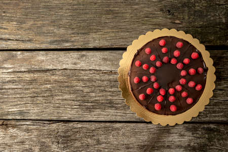 chocolate cake: Top view of delicious chocolate cake decorated with juicy fresh raspberries on old textured wooden desk with plenty of copy space on the left side.