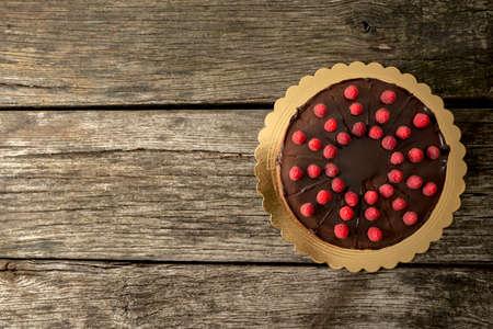 pastel de chocolate: Vista superior de un delicioso pastel de chocolate decorado con frambuesas frescas jugosas en escritorio de madera vieja con textura con un montón de espacio de la copia en el lado izquierdo.