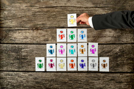 Leadership and team management concept with a businessman arranging a series of hand-drawn cards depicting people into a pyramid and just about to place the last card at the pinnacle in place.