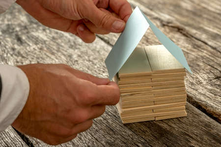 project property: Close up Male Architect Designing a House Miniature out of Small Pieces of Wood and Paper on Top of Wooden Rustic Table. Stock Photo