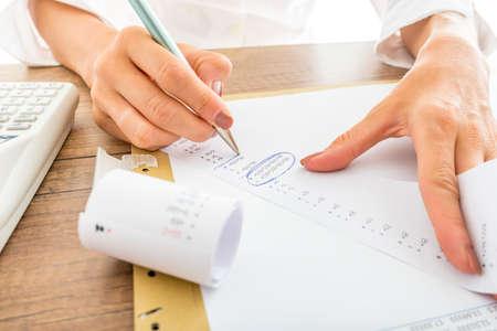 registros contables: Cierre de la empresaria Cálculo de Gastos en impresos de recibos en su escritorio con la calculadora en su lado.
