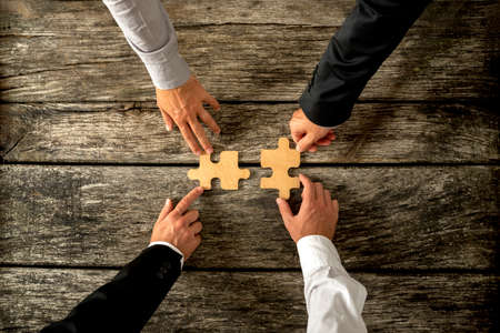 merging: Four successful business men joining two puzzle pieces each being held by two partners, rustic wooden background. Conceptual of merger or creative cooperation of two business companies.