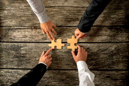 Wobei vier erfolgreiche Geschäftsleute Verbinden von zwei Puzzleteile, die jeweils von zwei Partnern, rustikale Holzuntergrund statt. Konzeptionelle der Verschmelzung oder der kreativen Zusammenarbeit von zwei Geschäftsunternehmen. Standard-Bild