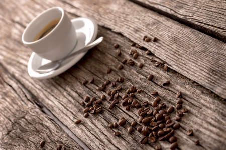 bean: Fresh roasted coffee beans and a cup of black filter coffee or espresso on a rustic wooden table viewed at an angle.