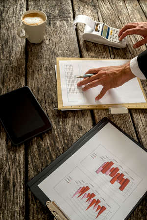 banking document: Hand of a Businessman Calculating Sales on Summary Report Using Printing Calculator on Top of a Rustic Wooden Table with Cup of Coffee, Tablet Computer and Document with Graphs.