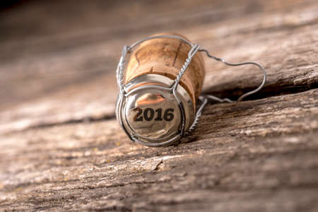 cork wood: 2016 champagne cork lying on a rustic wooden table in a New Year background, tilted angle with shallow DOF and copyspace.