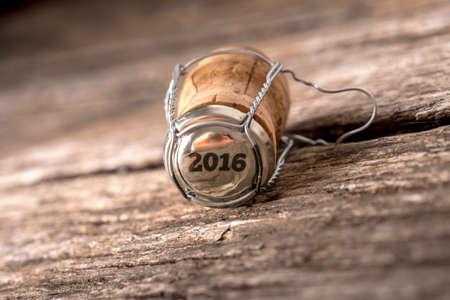madera r�stica: 2016 corcho del champ�n acostado en una mesa de madera r�stica en un fondo de A�o Nuevo, el �ngulo inclinado con el DOF bajo y copyspace. Foto de archivo
