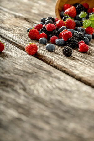 berries: Assorted fresh berries spilling from a bowl onto a rustic weathered wooden table, low angle view with foreground copyspace.