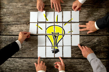 concept idea: High angle view of businessmen hands touching white papers arranged on a rustic wooden table forming a yellow light bulb. Conceptual for bright business ideas and innovations.