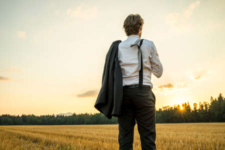 actitud: Exitoso hombre de negocios joven que se coloca en campo de trigo mirando mirando hacia el futuro mientras se decide sobre nuevas medidas e instrucciones para tomar en su carrera. Foto de archivo