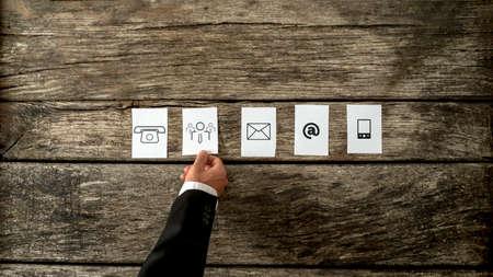 comunicação: Alto, ângulo de um empresário de colocar para fora cartões brancos com ícones de comunicação e pessoas em um fundo de madeira rústico.