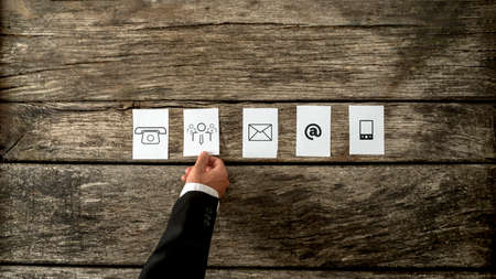 communication: High angle view of businessman laying out white cards with communication and people icons on a rustic wooden background. Stock Photo