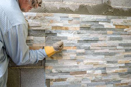 Un homme plus âgé décorer un mur avec des carreaux ornementaux pressage et fixateur une tuile fermement dans une colle avec son poing.