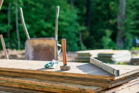 building materials: Construction Site concept with a wooden mallet, level and gloves on planks of wood outdoors in a forested area.