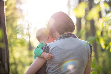 Young mother enjoying a beautiful moment of love, tenderness and care with her baby boy while walking through a sunlit park or forest in a conceptual image suitable for innocence, devotion and family.