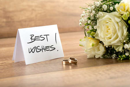 wedding wishes: Close up Attractive Fresh Flowers, Pair of Rings and Best Wishes Card for Wedding on Top of Wooden Table.