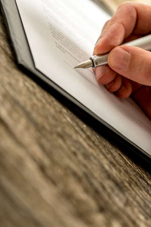 Closeup of male hand signing business contract, application, subscription form  or insurance papers with fountain pen on textured old rustic wooden desk.