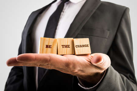Three wooden cubes in the palm reading Be the change, motivating you to go ahead and have the courage to make changes in order to grow and develop your personal life and career. Stock Photo