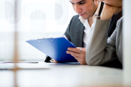ejecutivo en oficina: J�venes ejecutivos de negocios, un hombre de negocios y de la mujer, sentada en una oficina de comprobar una aplicaci�n o documento de preparaci�n para la entrevista con un nuevo empleado probable.