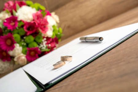 dedication: Wedding Register with Pen, Bride and Groom Rings and Bouquet of Fresh Beautiful Flowers on Top of a Wooden Table.