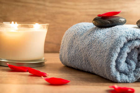 blue petals: Luxurious spa setting with a rolled blue towel, romantic candle and black massage stone decorated with red rose petals.