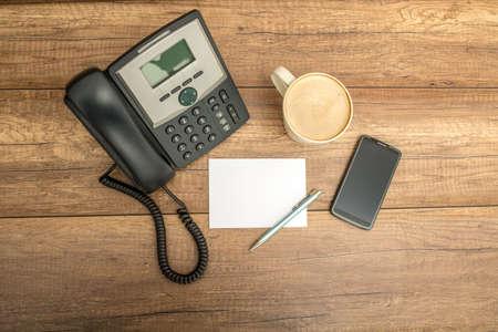 Bovenaanzicht van bureautelefoon, lege notitie papier, pen, een kop koffie en een slimme telefoon, op een houten tafel met copyspace.