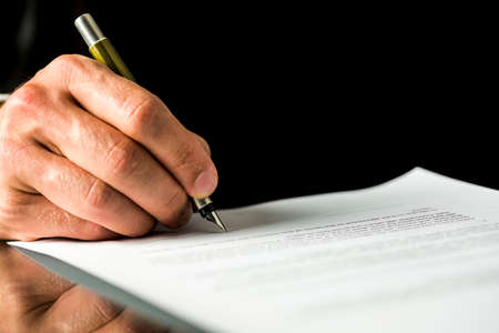 Closeup of male hand signing a contract, employment papers, legal document or testament. Isolated over black background.