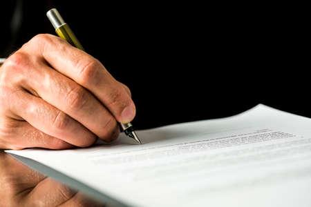 Nahaufnahme der männlichen Hand Unterzeichnung eines Vertrages, Arbeitspapiere, Urkunde oder Testament. Auf schwarzem Hintergrund isoliert.