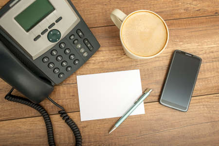 Corded black desk phone, blank note paper, pen, a cup of cappuccino and a smart phone, on a wooden table, high-angle shot. Banque d'images