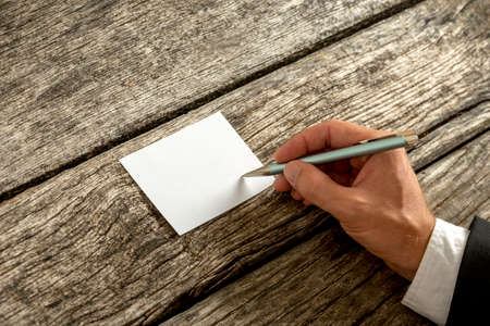writing paper: Overhead view of a hand in elegant suit writing on blank white card or paper with ballpoint pen on weathered old wooden desk, with copy space for you text. Stock Photo