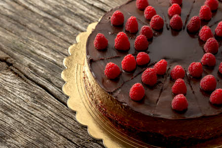 indulge: Overhead view of tasty raw chocolate cake decorated with raspberries inviting you to indulge yourself into sweet temptation, placed on a golden plate and textured rustic wooden desk. Stock Photo