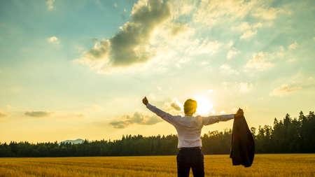 Junge ehrgeizige Exekutive genießt und feiert seinen Geschäftserfolg, als er steht in schöner Natur unter majestätischen Himmel mit seinen ausgebreiteten Armen weit verbreitet hält seinen Daumen nach oben.