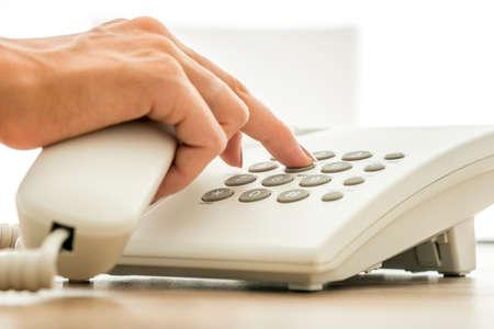 secretaria: Vista de cerca de secretaria de marcar un número de teléfono en el teléfono fijo blanco. Conceptual para la comunicación global, soporte técnico y servicio al cliente.