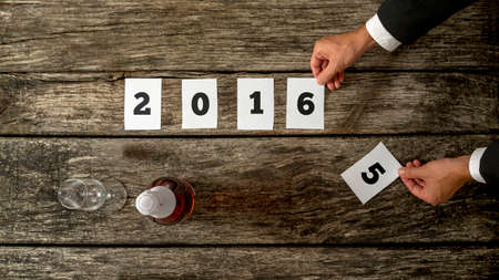 anticipating: Businessman celebrating year 2015 anticipating coming year 2016 as he changes number 5 for number 6 on 2016 date on papers lying on rustic wooden desk with champagne bottle and glass on the side. Stock Photo