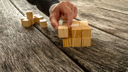 challenges: Closeup of businessman assembling blank wooden cubes into a structured whole on antique wooden desks. Conceptual of business start up, vision and strategy.