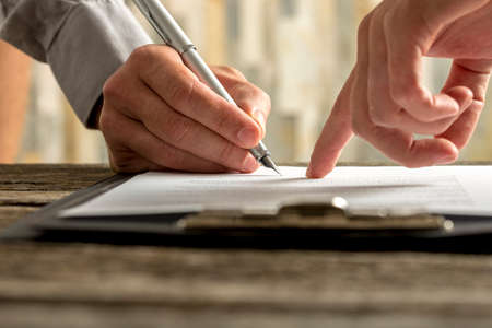 firmando: Detalle de empresario mostrando su nuevo socio de negocios, donde a firmar un acuerdo o contrato con la pluma en la mesa de madera rústica. Foto de archivo