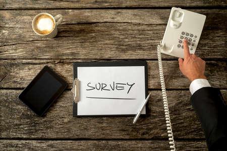 Obenliegende Ansicht der Telefonistin machen Befragung am Telefon mit einem Blatt Papier, Tablet PC, Handy und eine Tasse Kaffee auf seinem rustikalen hölzernen Schreibtisch. Konzept der Telemarketing-und Kunden-Feedback. Lizenzfreie Bilder