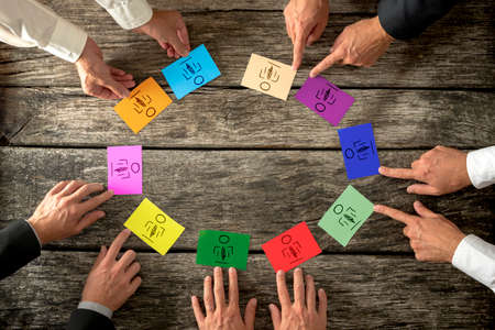 two hands: Business leaders creating diverse and competent business team seated around a wooden table each pointing to two brightly colored cards with hand doodled person, overhead close up of their hands.