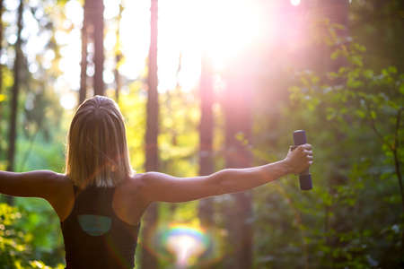 Young blonde woman working out with dumbbells in beautiful nature with her back to the camera and arms widely spread. Conceptual of exercise and body care.