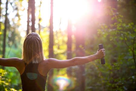 Mladá blonďatá žena pracuje se s činkami v krásné přírodě zády ke kameře a paží široce rozšířen. Koncepční cvičení a péče o tělo.