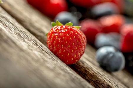 tilted view: Low angle tilted view of a luscious ripe red strawberry on a rustic wooden table with assorted fresh berries visible in the background.