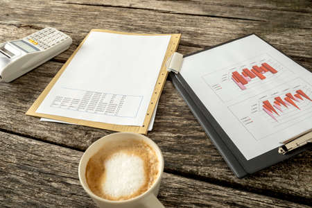 banking document: Tax and finance concept - paperwork with graphs, charts, data and numbers, adding machine and a cup of fresh hot cappuccino on a textured rustic wooden desk. Stock Photo