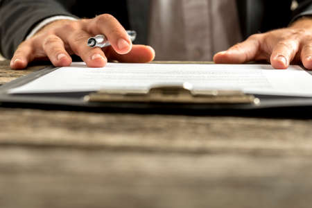 Closeup of male hand about to sign a subscription or application papers clipped on blue folder on wooden desk.