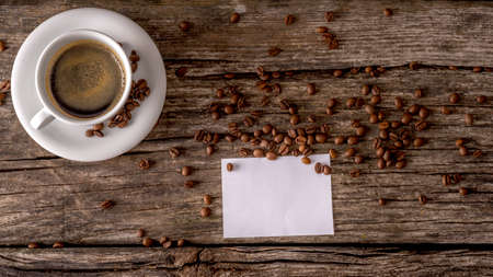 black boards: Overhead view of cup of freshly prepared black coffee and blank white message card on a textured wooden boards, coffee beans scattered all over the table.