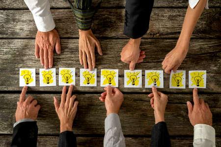 Brainstorming a koncepce týmové práce se skupinou různých podnikatelů každý natáhl kartu s zářící žárovky uspořádány v řadě koncepční nápadů, inspirace a inovací. Reklamní fotografie