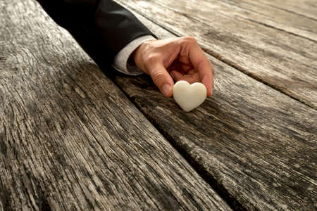 heart in hand: Male hand in elegant suit holding heart made of white marble against a textured wooden background. Conceptual of love, romance and proposal.