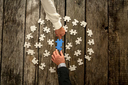 Teamwork in business concept with two businessmen around a circle of scattered white puzzle pieces cooperating to construct a blue jigsaw in the centre, close up of their hands and wooden table.