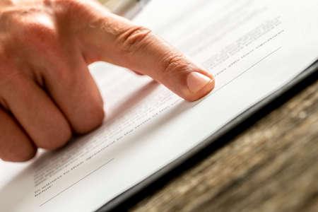 Homme d'affaires en attente d'une signature sur un contrat ou entente pointage avec son doigt vers le bon endroit pour signer, vue rapprochée faible angle du document et son doigt. Banque d'images